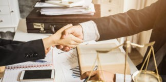FB: The picture displays 2 hands having an agreement in an office.