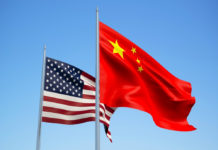 Wibest – Current Stock Market: United States and China flags waving in the wind.