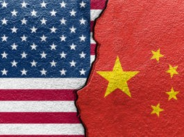 United States and China's flags on cracked wall.
