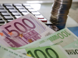 Wibest – Euro: Euro bills, coins and a calculator.