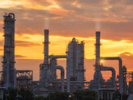 Petroleum Products: Pipeline and oil tank with sunrise.